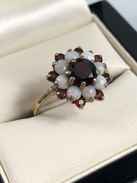 Lot 4 - 9ct gold opal and garnet halo ring