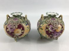 Pair of Continental hand painted vases on Tripod feet with raised decoration approx 10cm tall