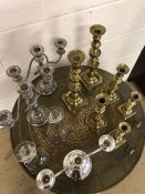 Collection of Glass, Silver plated and Brass candlesticks over two shelves