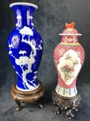 Two Chinese vases, a blue and white vase and a Famille Rose lidded jar both with carved wooden