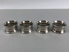 Four matching heavy 255g silver coloured napkin rings the makers marks for John Somers