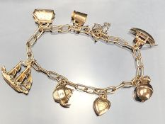 9ct Gold charm bracelet with seven gold charms (the boat marked for 14ct). total weight approx 12.
