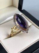 18ct Gold Marquise ring set with an Oval Amethyst stone and surrounded by square cut Diamonds