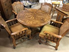 Circular extending dining table on pedestal base with four turned legs, along with four carver