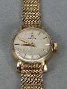 Ladies 9ct Gold OMEGA wristwatch with silver coloured dial and 9ct 375 strap (total weight 23.4g)
