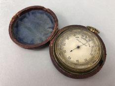 Brass cased pocket barometer inscribed 'Compensated', approx 5cm in diameter, in original leather