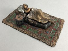 Cold painted bronze of a nude sleeping lady in a bed on a carpet, approx 16cm in length