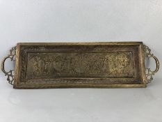 Oblong brass embossed tray with remnants of original colour pigments, two handles, depicting