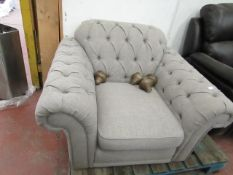 Grey Fabric Button Back arm chair with wooden feet.