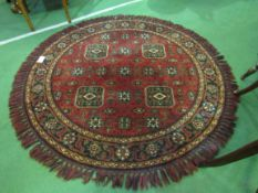 Round deep pile fireside rug in deep red with lozenge design.