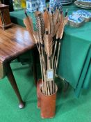 Collection of primitive fletched arrows in modern leather quiver.