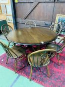 Ercol drop side dining table together with six Ercol Windsor style chairs.