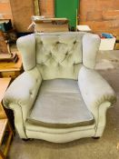 A large green upholstered Victorian armchair on casters.