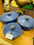 Three blue Le Creuset casserole dishes.