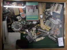 Display case of penknives, watches, costume jewellery, letter from the Queen