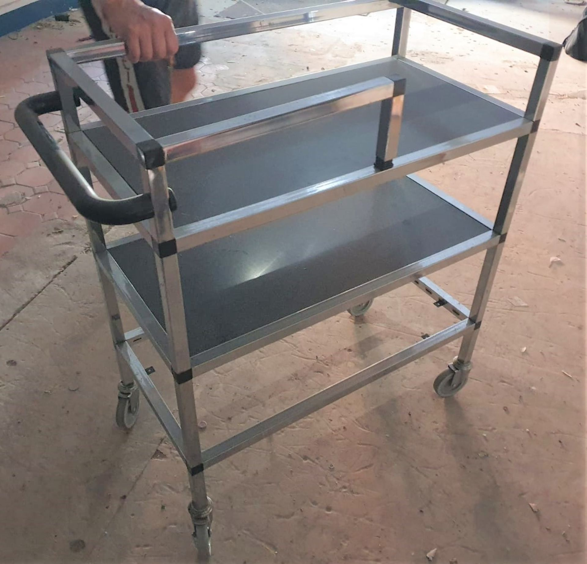 Lot 7551 - 1 x Mobile Trolley With Pull/Push Handle and Castors - Chrome Finish With Black Shelves - CL515 -