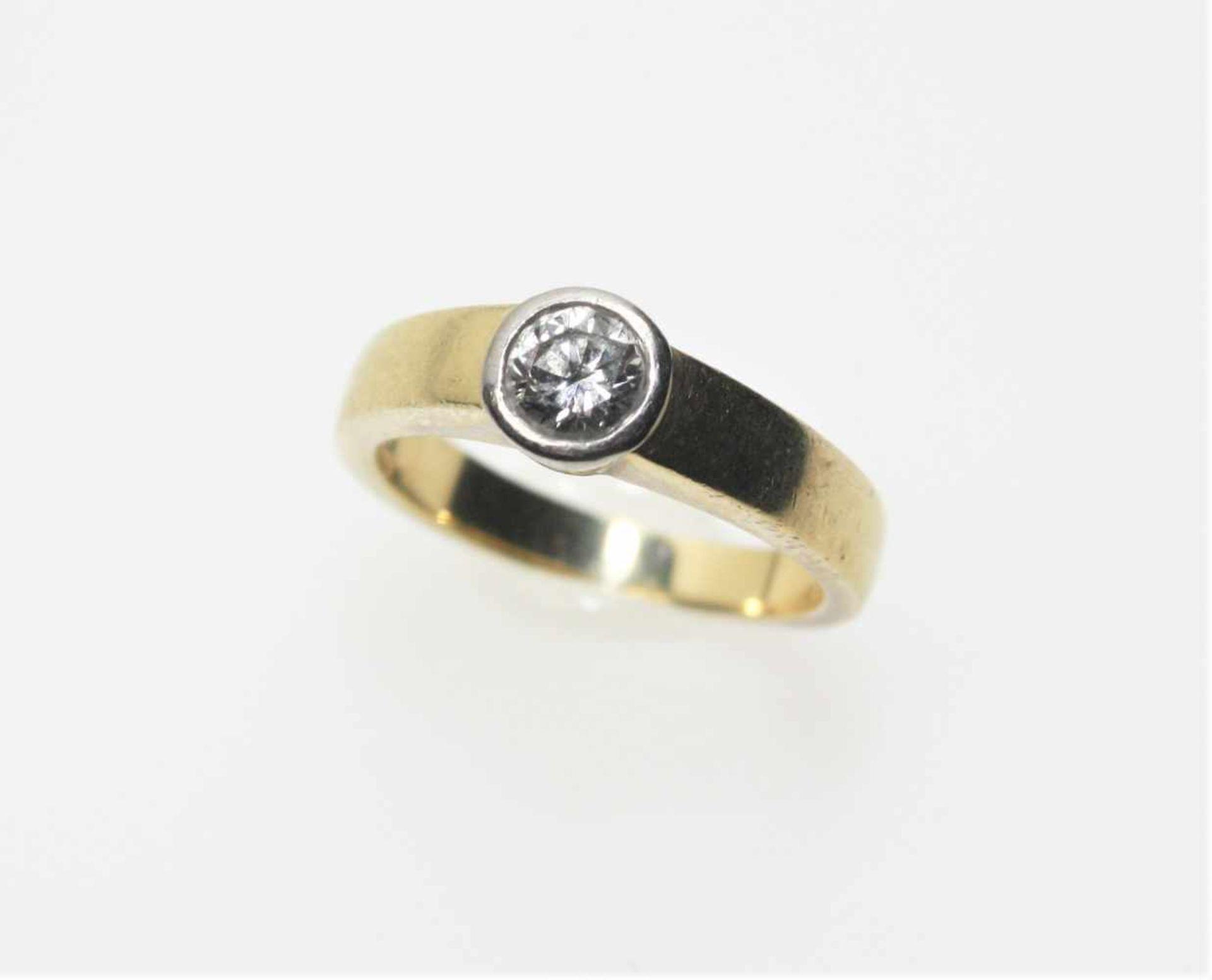 Los 27 - Goldener Ring 750/f gest., in Weißgoldzarge ein Diamantsolitär in Brillantschliff ca. 0,52 ct in