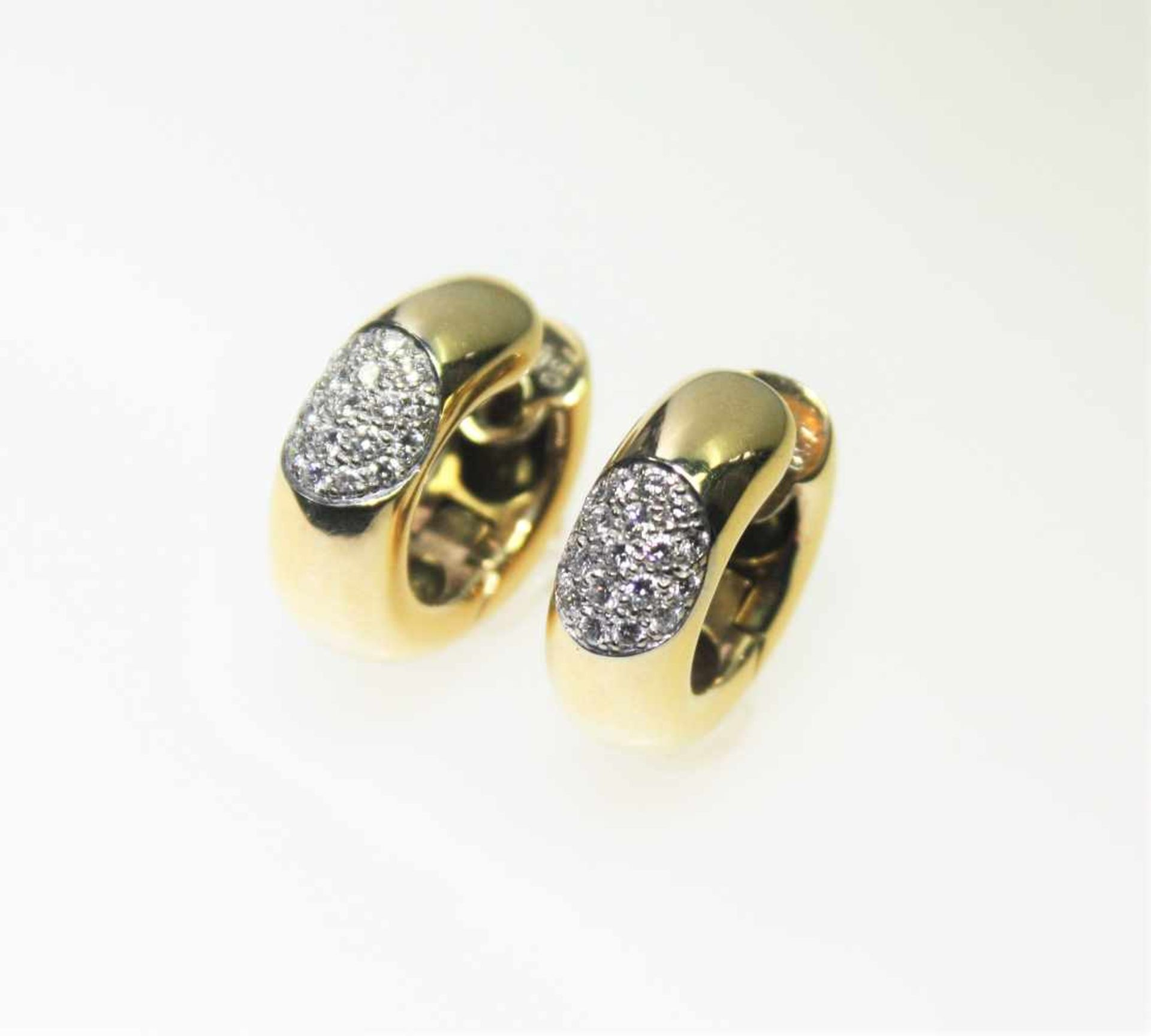 Moderne, goldene Creolen 750/f gest., im Vorderteil jeweils ein Oval ausgefasst mit Diamanten in