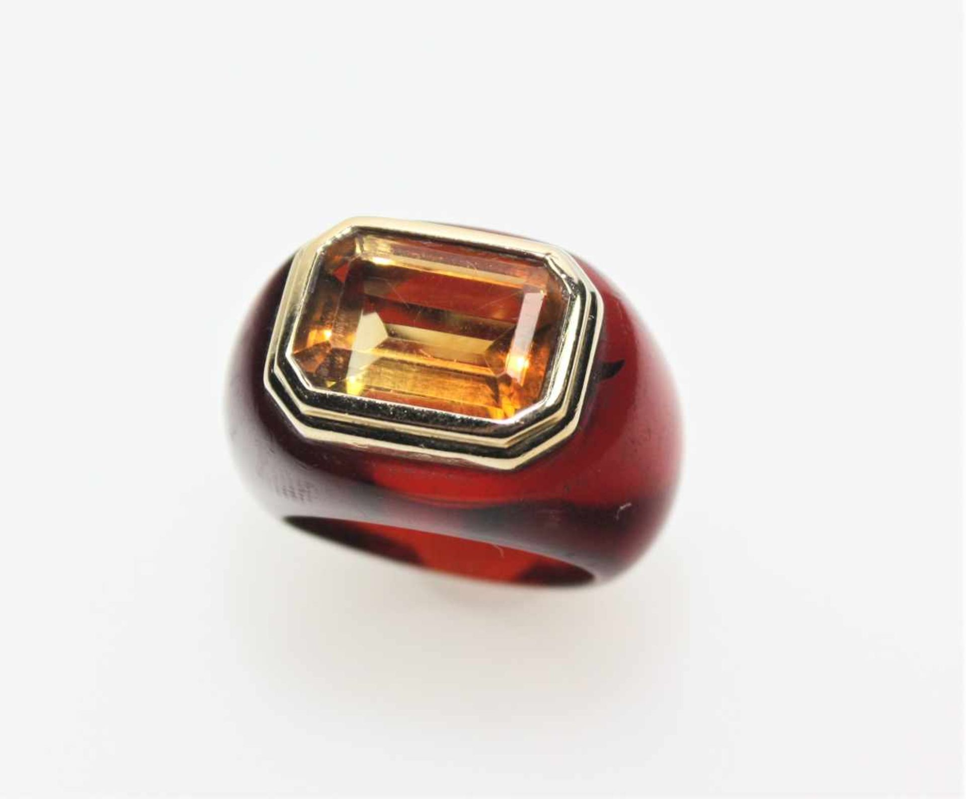 Moderner Bandring aus rotbraunem Kunststoff, in goldener Zarge ca. 585/f ein achteckiger Citrin (