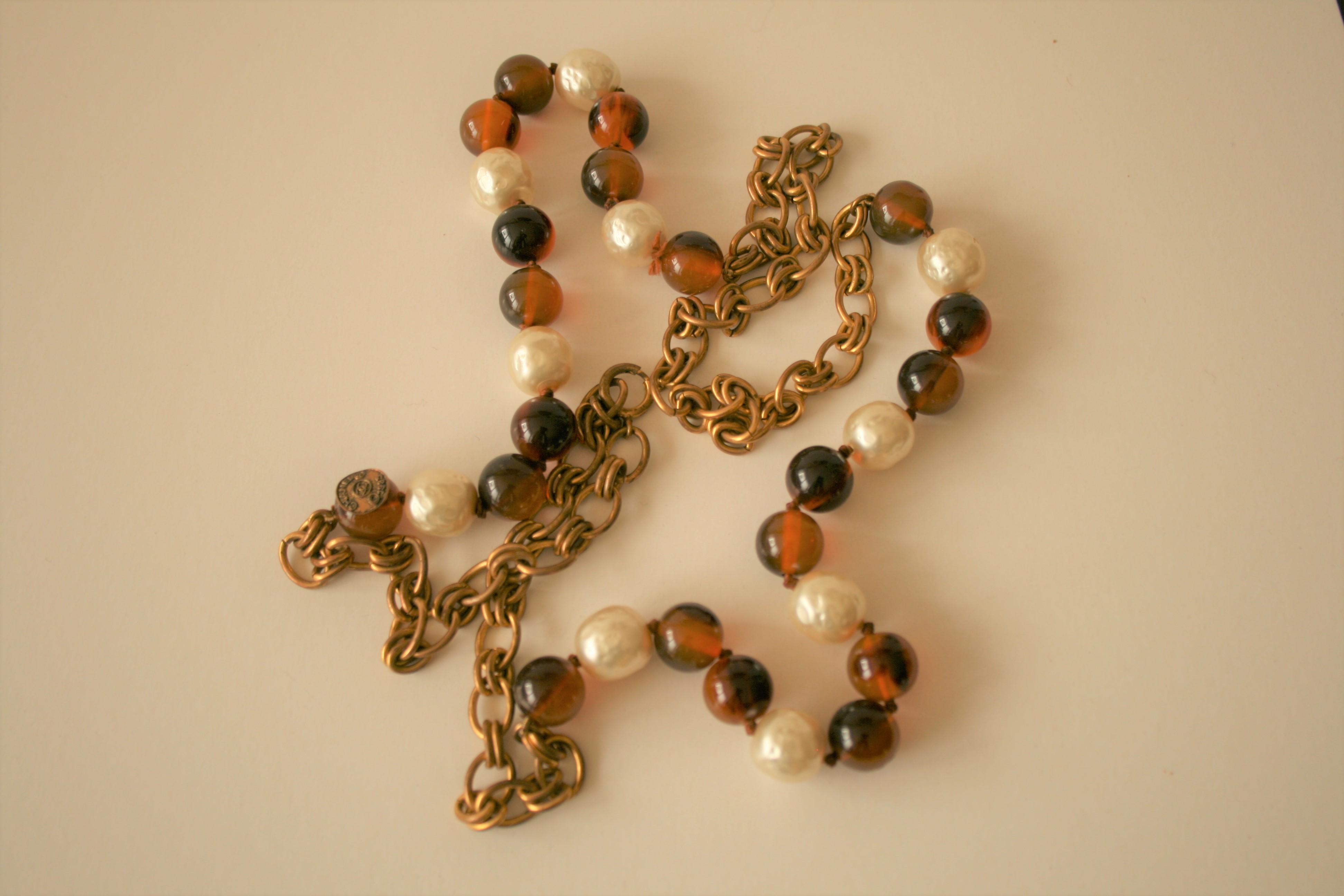 Lot 26 - Collier long de billes en verre brun et perles en résine, maillons couleur bronze, [...]
