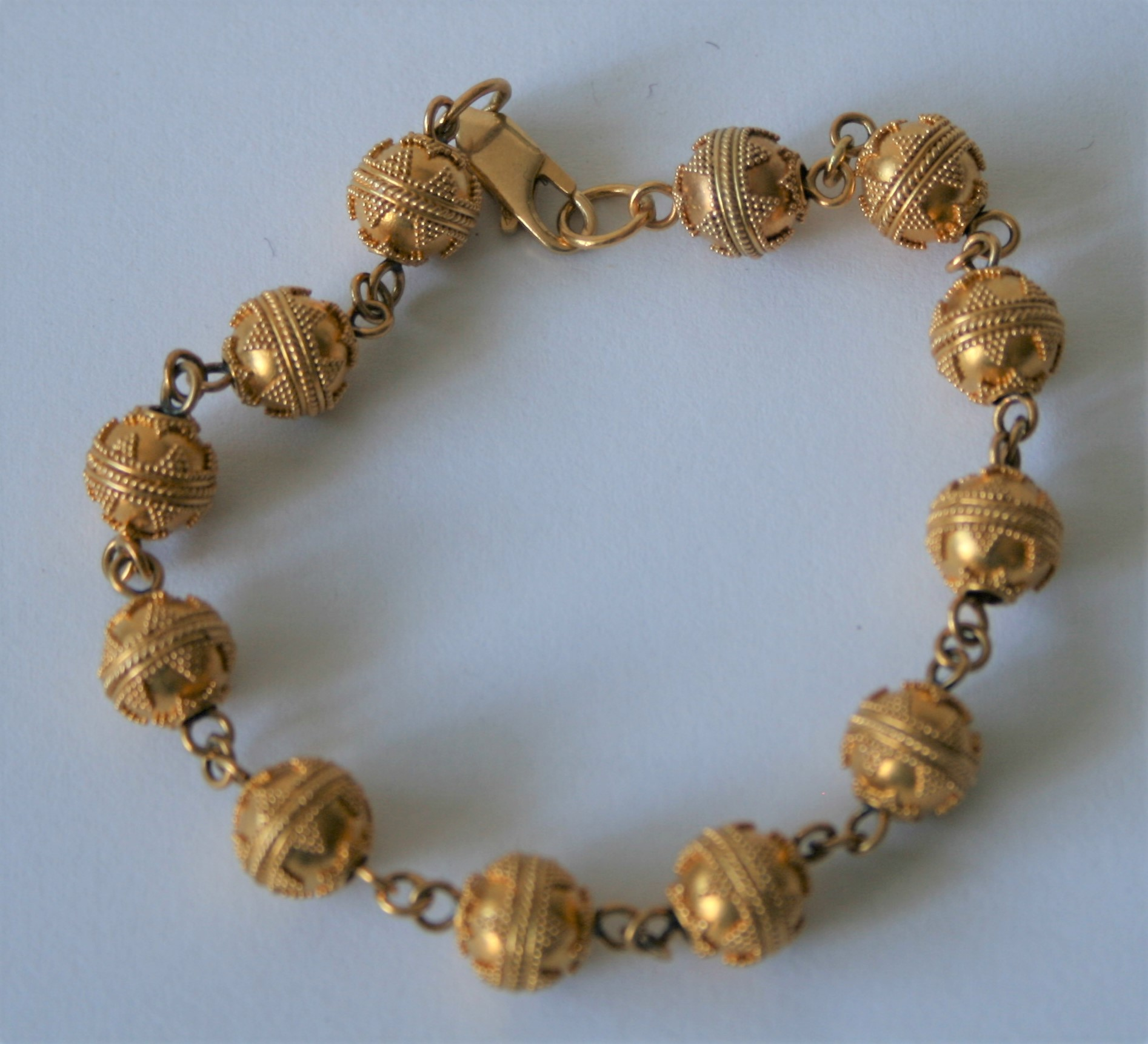 Bracelet en or 18 ct composé d'une succession de 12 boules gravées de motifs [...]