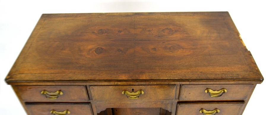 Lot 373 - A George I style walnut kneehole desk