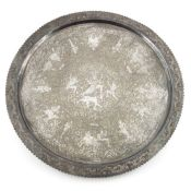 A large Indian white metal tray, circular form, chased and engraved with various figures within a fo
