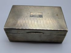 An early 20th century silver cigar case, engine turned outer, dragon crest, hallmarked London 1926-