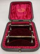 A pair of silver knife rests with case, hallmarked Sheffield, 1900, 90g, L.8cm