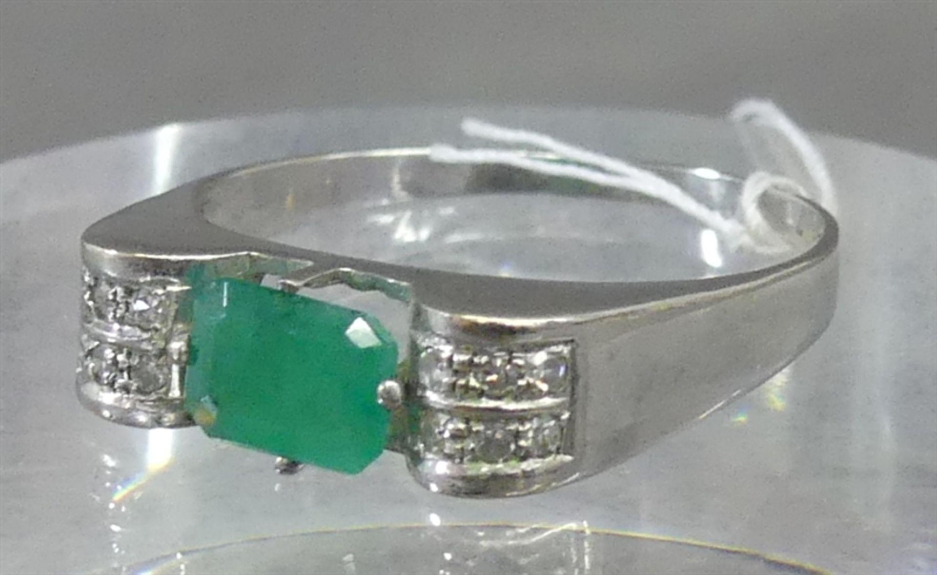Damenring 14 kt. Weißgold, 1 Smaragd, Emeraldcut, 12 kl. Diamanten als Besatz, ca. 4 g schwer, RM