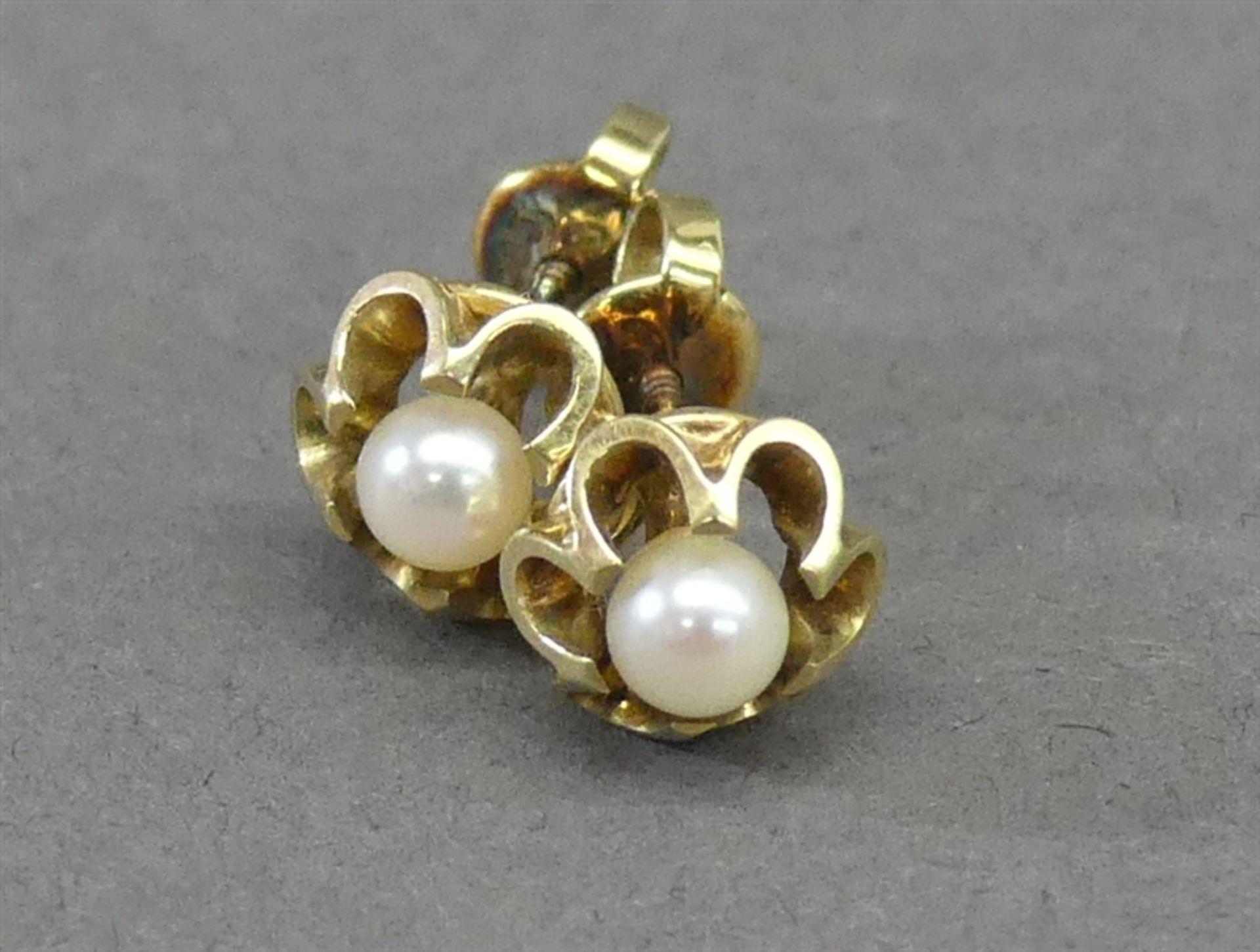 Paar Ohrstecker 14 kt. Gelbgold, 2 kl. weiße Perlen, durchbrochen gearbeitet, ca. 3 g schwer,