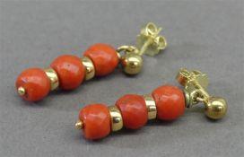 Paar Ohrhänger 14 kt. Gelbgold, 6 geschliffene Korallperlen, ca 6g, h 3 cm,