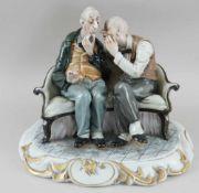 Männer beim angeregten Gespräch auf einer Bank sitzend, fein bemaltes Porzellan, auf der<b