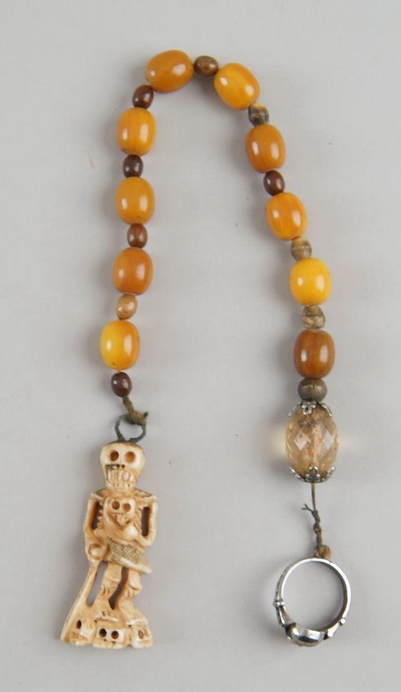 Faulenzer / Zehner Gebetskette mit Silberring und in Bein geschnitztem Skelett, einenTotenkopf tragend, L 36cm