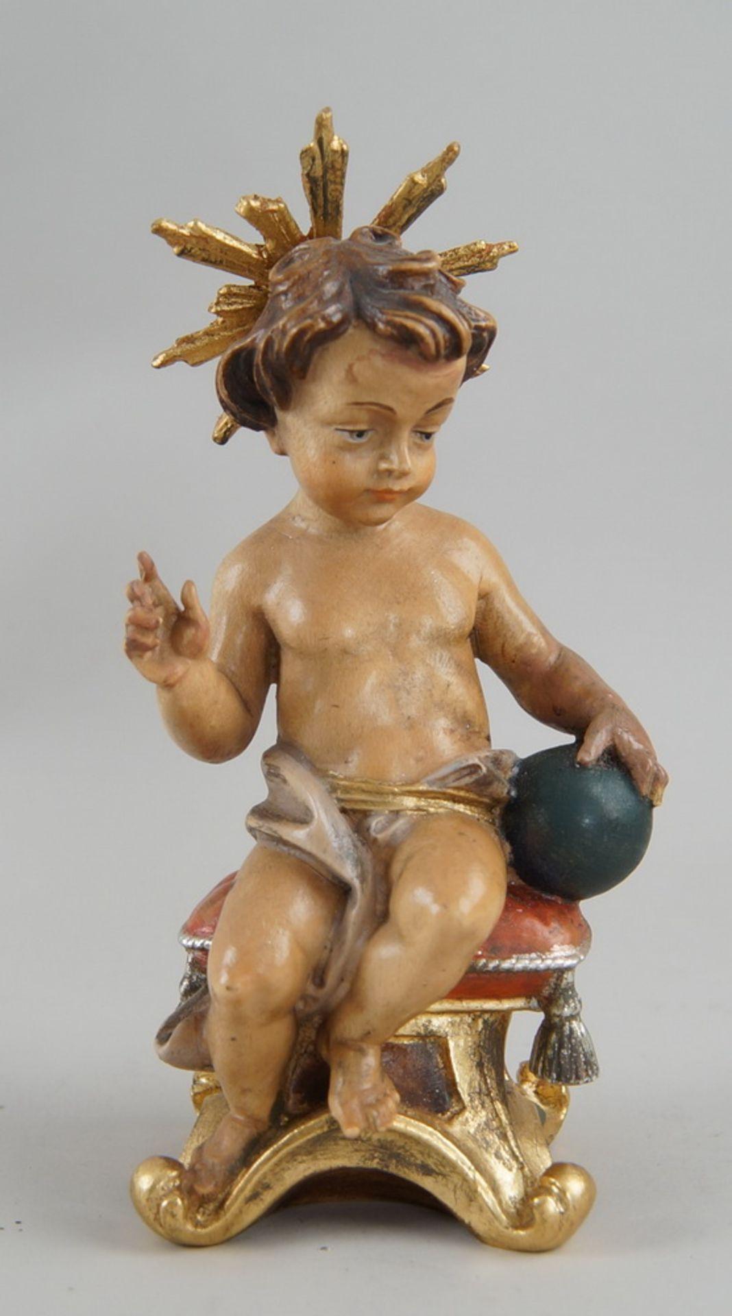 Los 3 - Sitzendes, liebliches Jesuskind mit Strahlenkranz und Weltkugel, Holz geschnitzt undgefasst, H19,