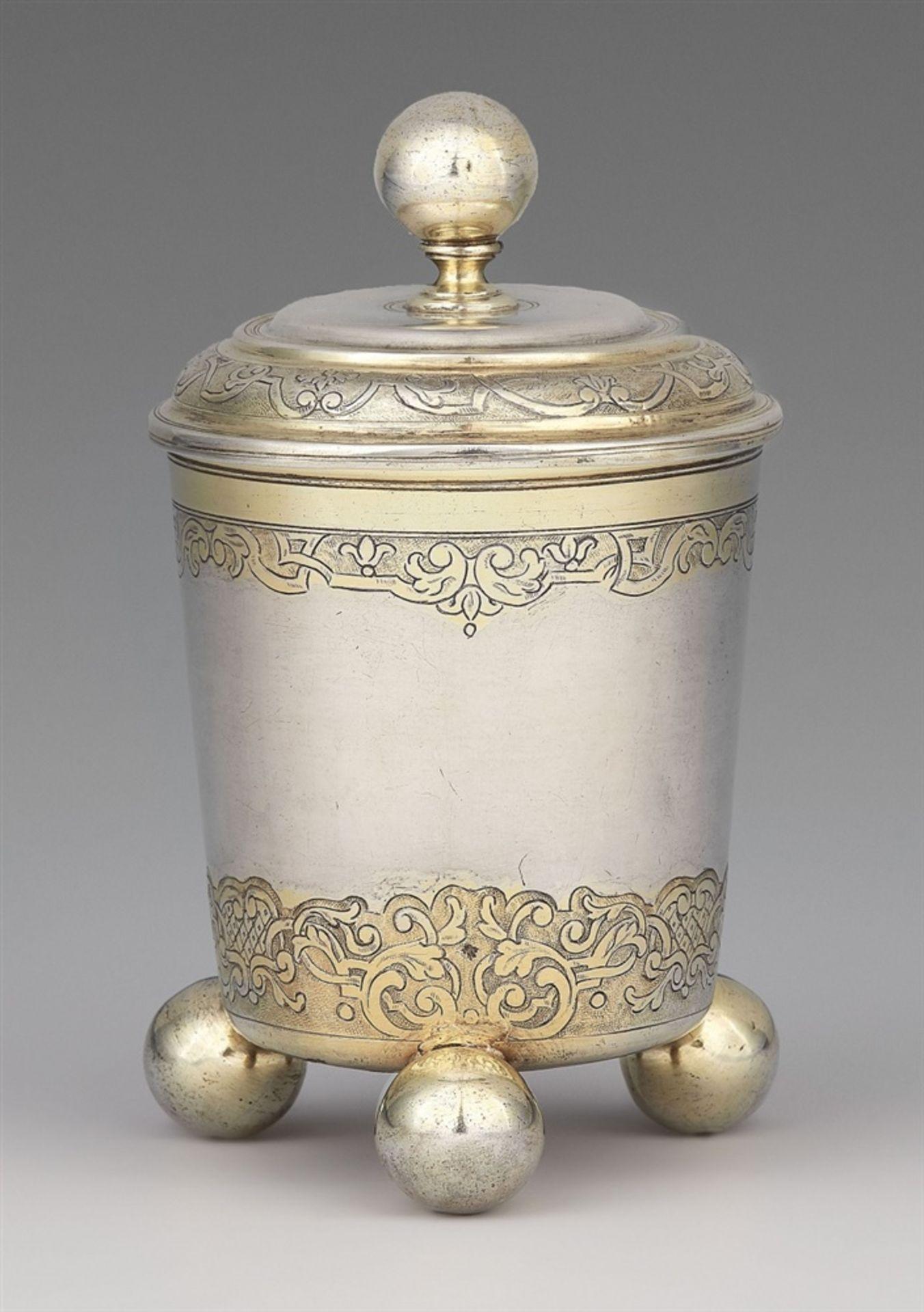 Los 725 - An Augsburg Règence silver beakerSilver; partly gilded. Parcel-gilt silver beaker on three spherical
