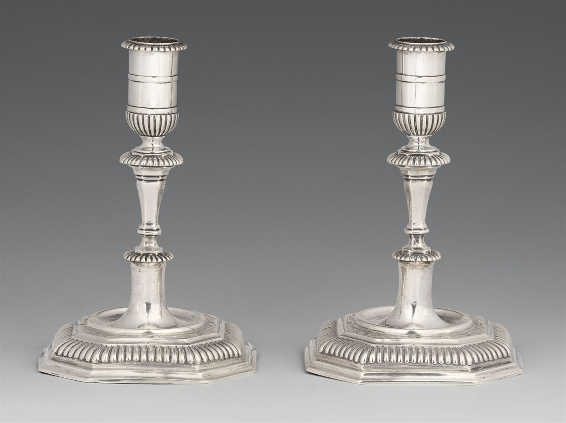 Los 745 - A pair of Halberstadt silver candlesticksSilver. Baluster-form shafts issuing from square