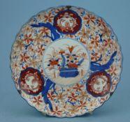 Inari-Teller, Japan, um 1900rund gewellter Rand, floraler Dekor in blau-rot, teilvergoldet, Dm 28,