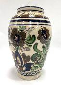 A Persian tin glazed vase, foliate decorated upon a cream ground, signed to the base Katona Mihaly
