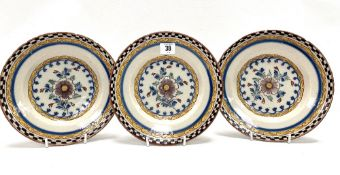 A set of three 18th century polychrome Delft dishes, each painted with a flower to the centre,