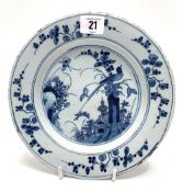 An 18th century English Delft dish decorated to the centre with a Ho Ho bird on a tree stump with