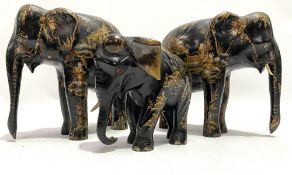 A pair of 19th century Chinese black lacquer gilt painted opposing elephants, decorated with figures