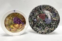 A Persian ware black transfer printed and painted circular dish, together with a fruit painted
