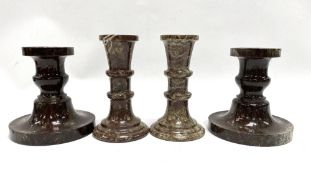 Two pairs of Cornish red turned serpentine candlesticks, the tallest 12.5cm.