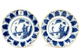 A pair of 18th century English blue and white Delft plates, both decorated to the centre with a