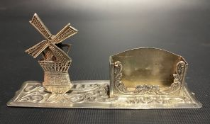 Continental white metal match box holder with articulated windmill and on a foliate embossed base,
