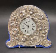 Modern silver mounted timepiece embossed with cherubs and fruiting vine with a quartz timepiece,