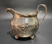 Edwardian silver foliate embossed cream jug with C scroll rim raised on four ball feet, Birmingham