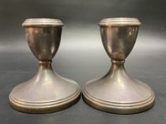 A pair of modern silver squat candlesticks with weighted bases.