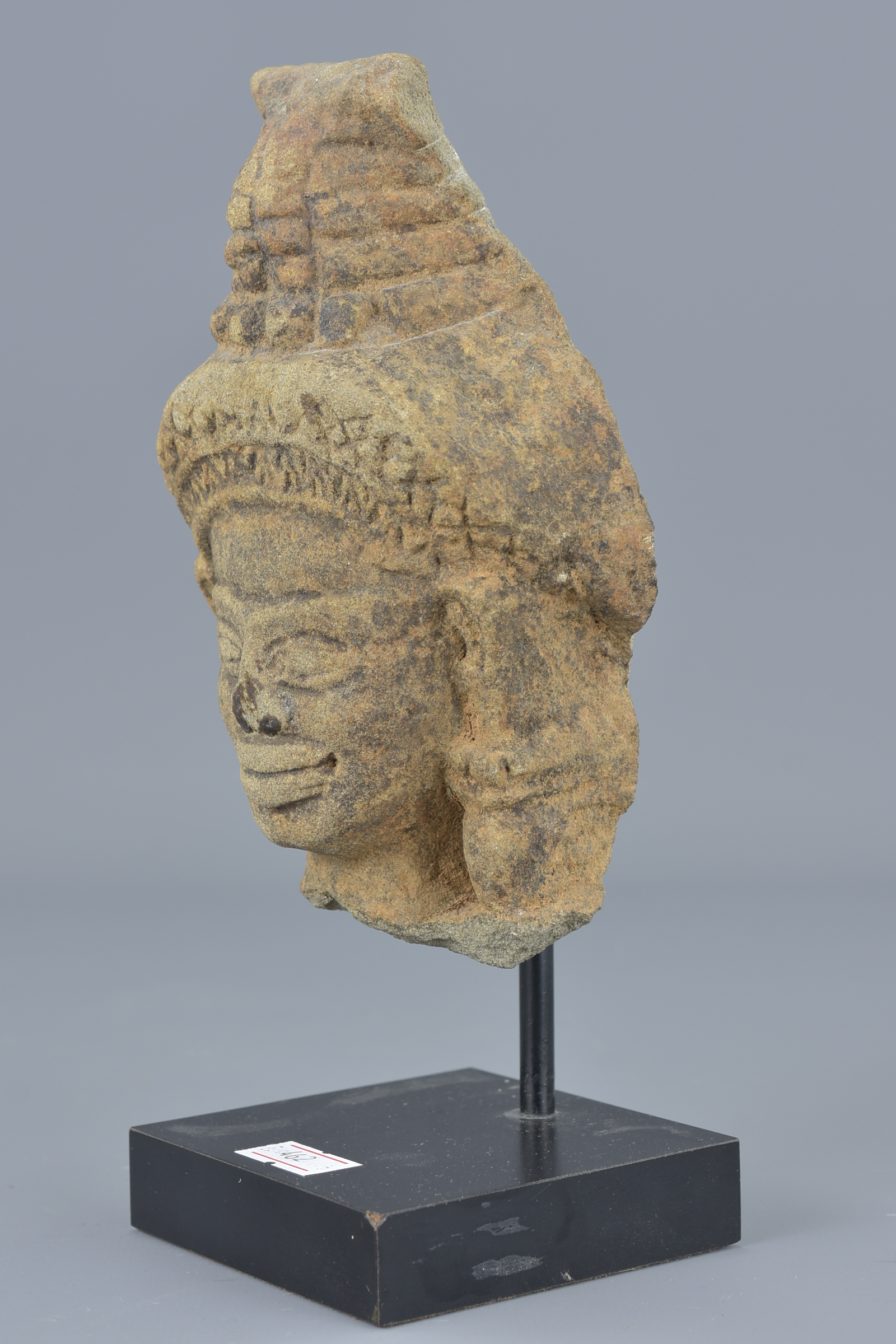 Lot 72 - A 19th century possibly Cambodian sandstone carving on display stand. Head 15cm x 9cm